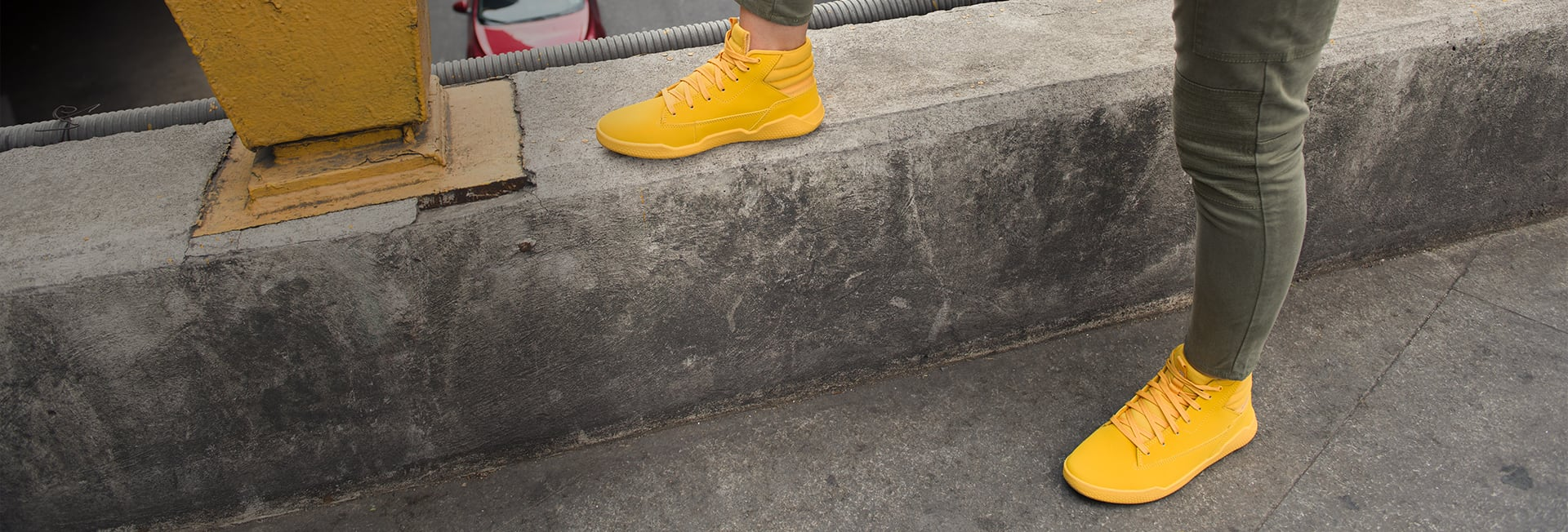 A person wearing yellow Cat Code shoes standing on cement.
