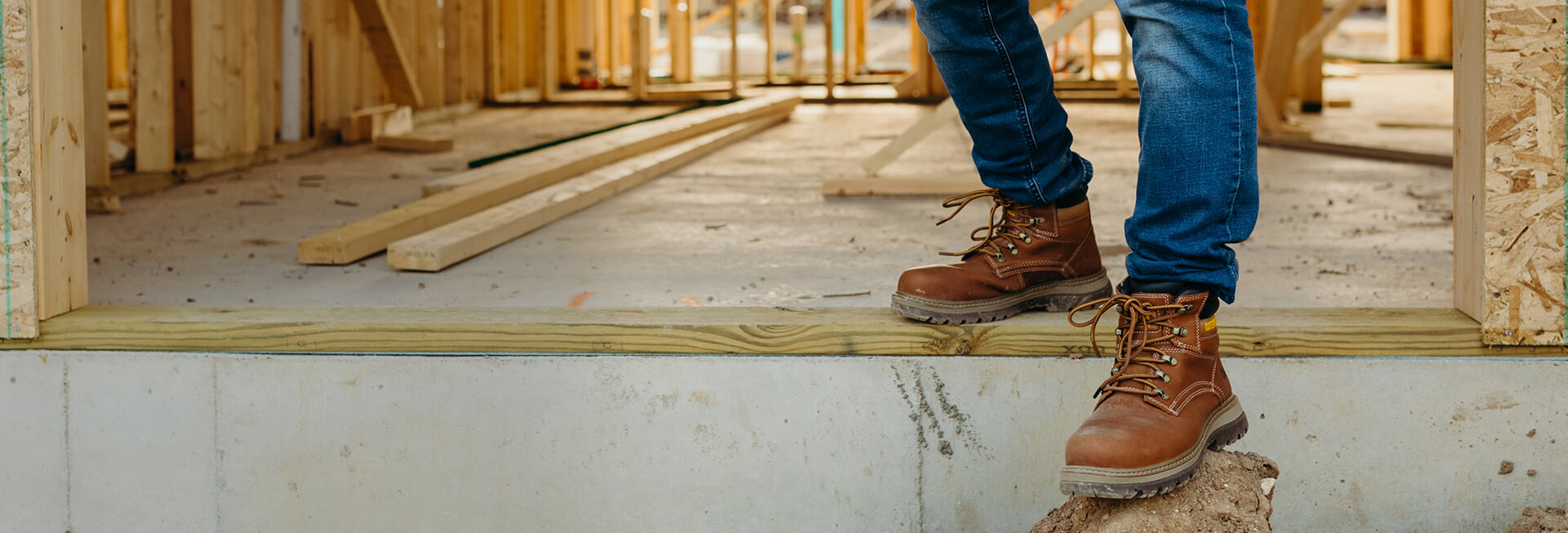 A person wearing tan, ankle-height boots steps down out of a new home under construction.