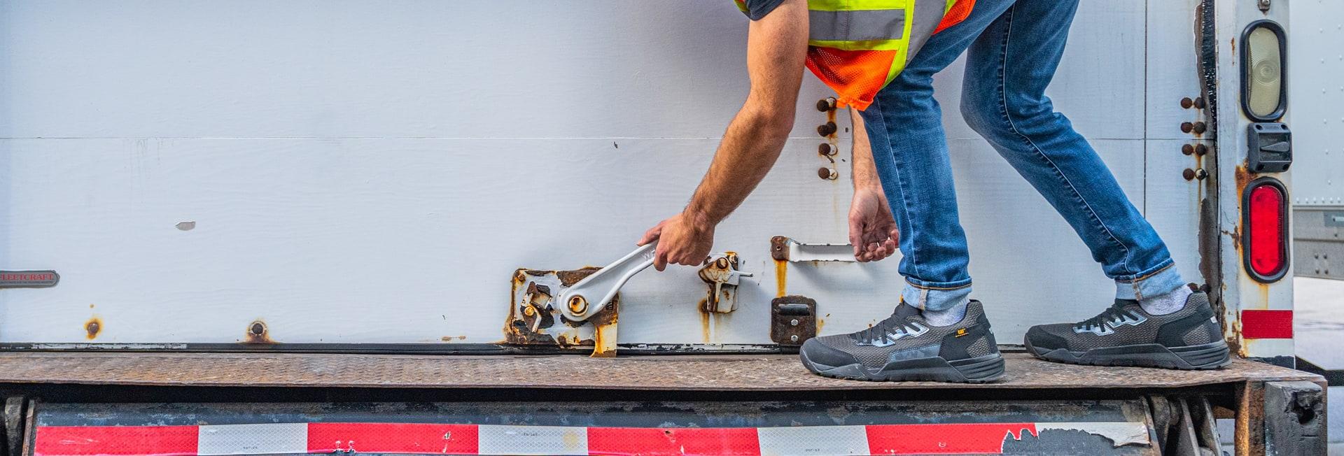 A worker opening a truck door, wearing Cat Sprint work shoes.