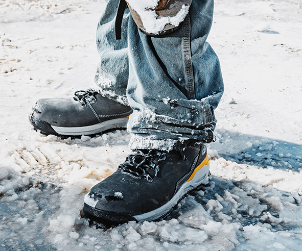 Men's feet wearing winter boots on ice and snow.