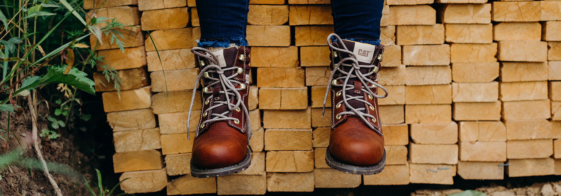 Feet, in leather work boots, dangling in front of a stack of lumber.