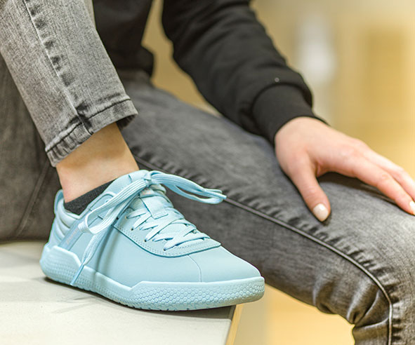 A light blue shoe born by someone putting their foot up while wearing a black jacket and grey pants.