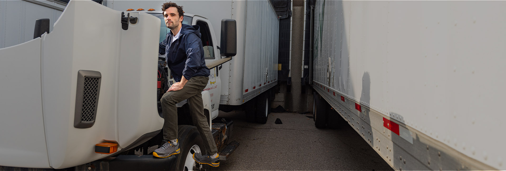 A man stading next to a semi truck.