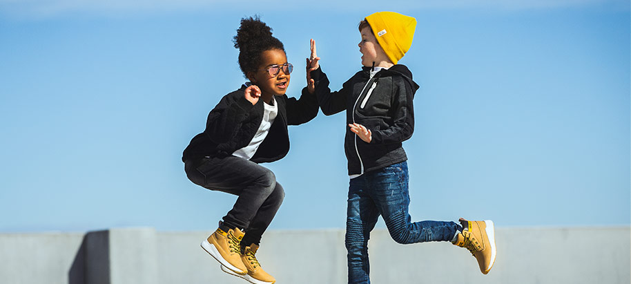 2 kids high-fiving in mid jump in their Colmax sneakers.