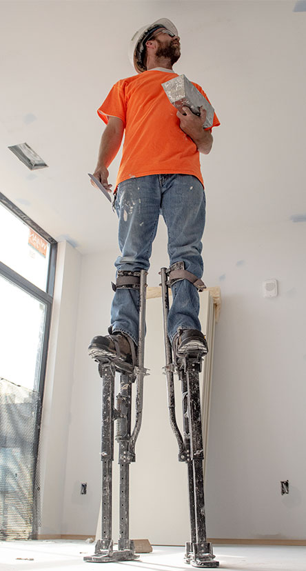 Man standing on stilts working on a ceiling.