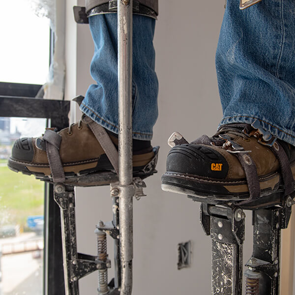 Boots standing on a pair of drywall stilts.