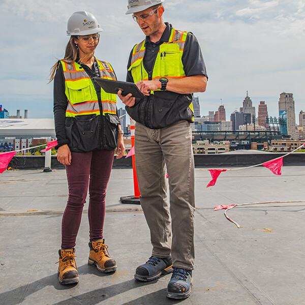 Two people standing on a job site, looking at a clipboard. They have some sweet kicks.