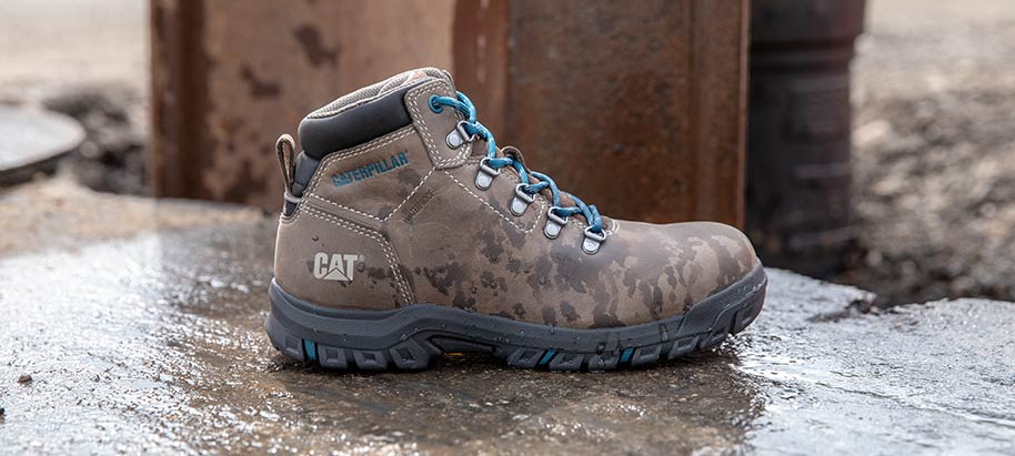 Camoflage waterproof boot with blue laces on concrete