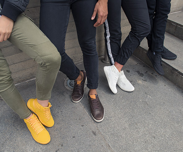Four people's legs each wearing different collored CAT Code leather sneakers.