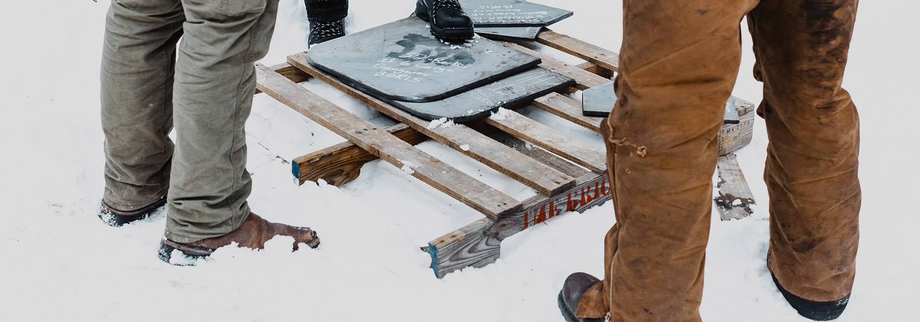 People standing around a wooden palet in the snow, wearing insulated leather CAT boots.