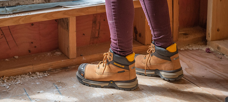 Woman wearing tan workboots on a construction site.