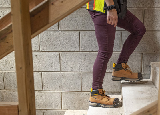 A woman walking up the stairs wearing steel toed boots in a cement block hallway.
