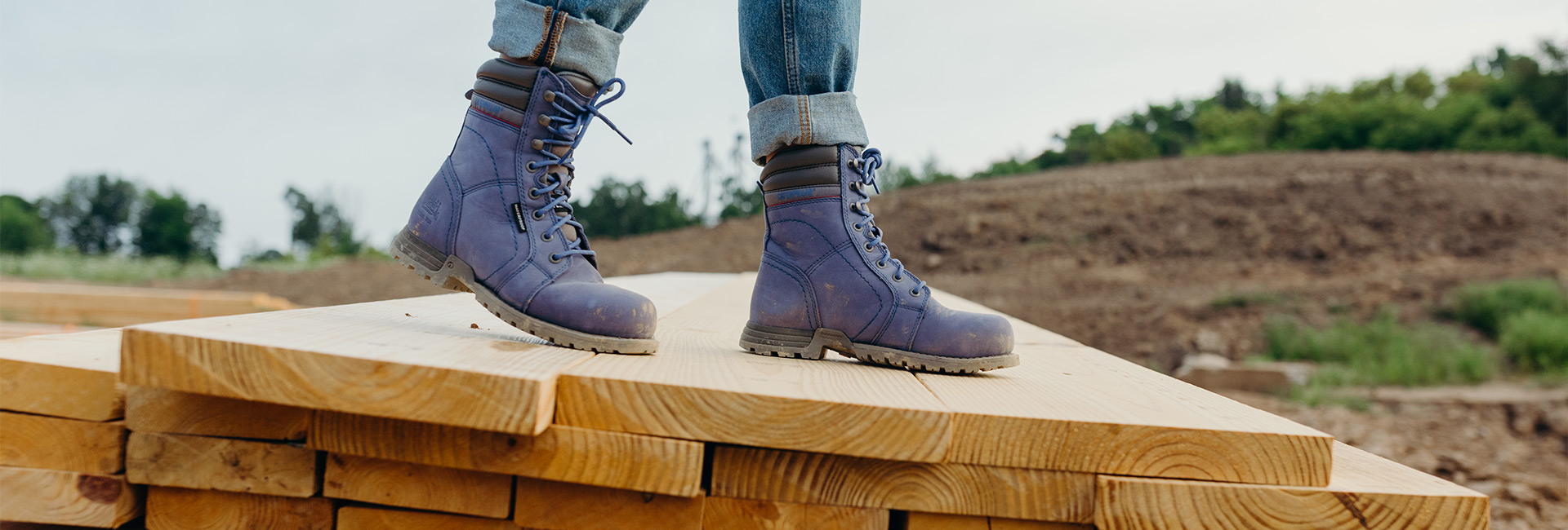 Woman wearing purple CAT workboots on a construction site.