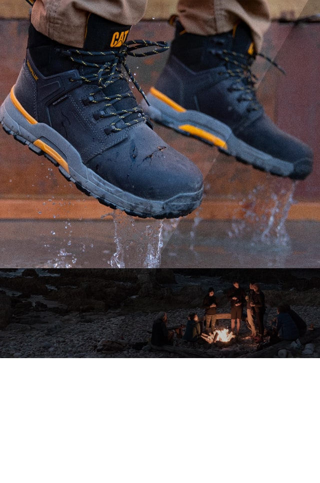 A person jumping in a puddle wearing CAT Edge boots and some people gathered around a fire.