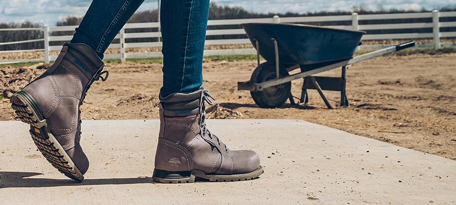Feet, in boots, on the farm, by a wheelbarrow