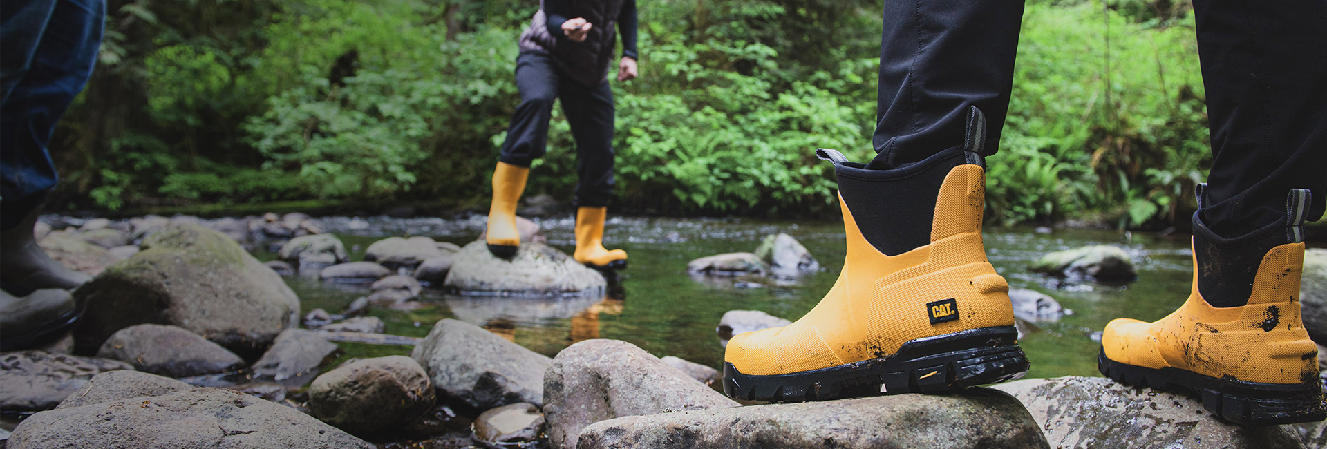 People standing on rocks in a stream, wearing different types of yellow and black waterproof shoes.