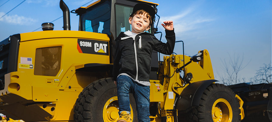 Boy jumping in front of a CAT tracktor.