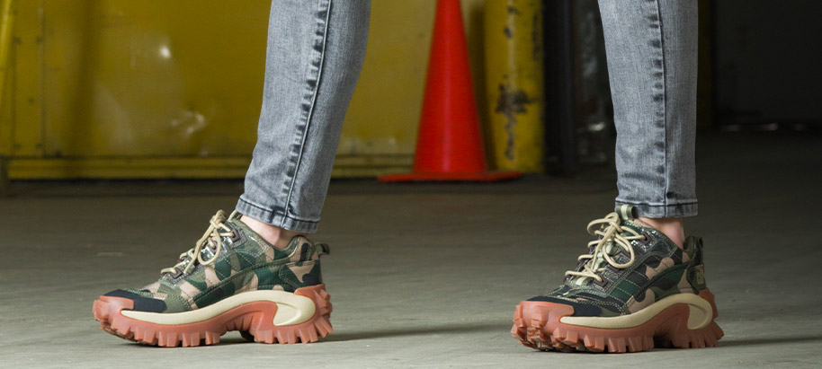 A women in an industrial setting wearing camouflage chunky 80's-style sneakers.