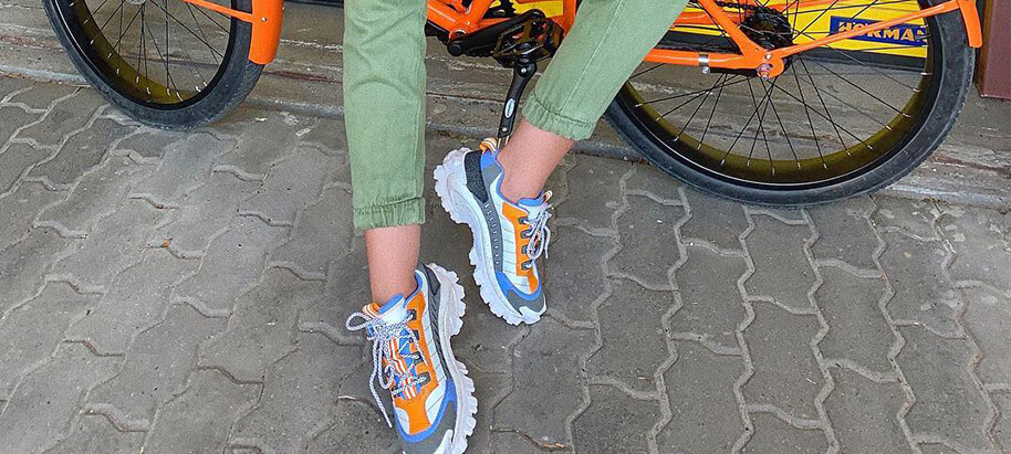 Someone leans against a bike. They may not know how to ride, but their shoes are fancy!