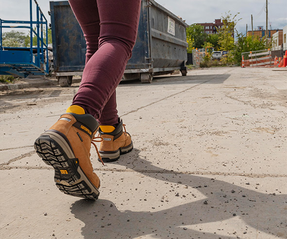 Excavator boots worn by a female, walking into the construction site.