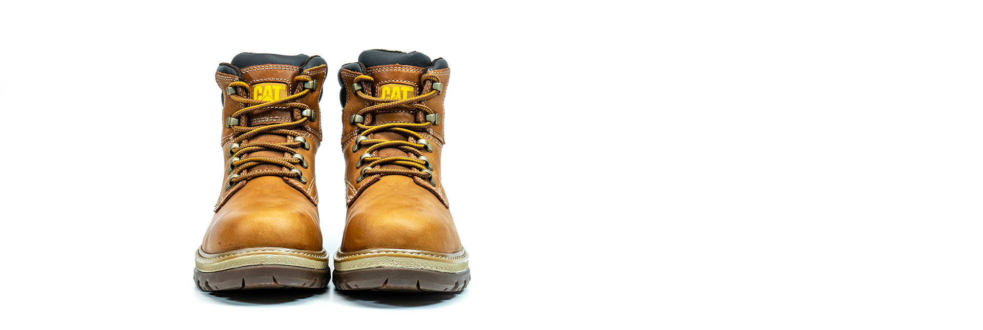 Pair of leather light brown CAT workboots facing the viewer