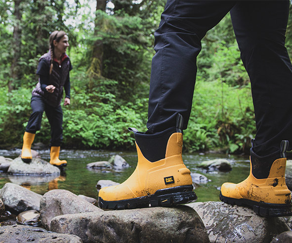 Person wading in a shallow body of water in their yellow stormers.