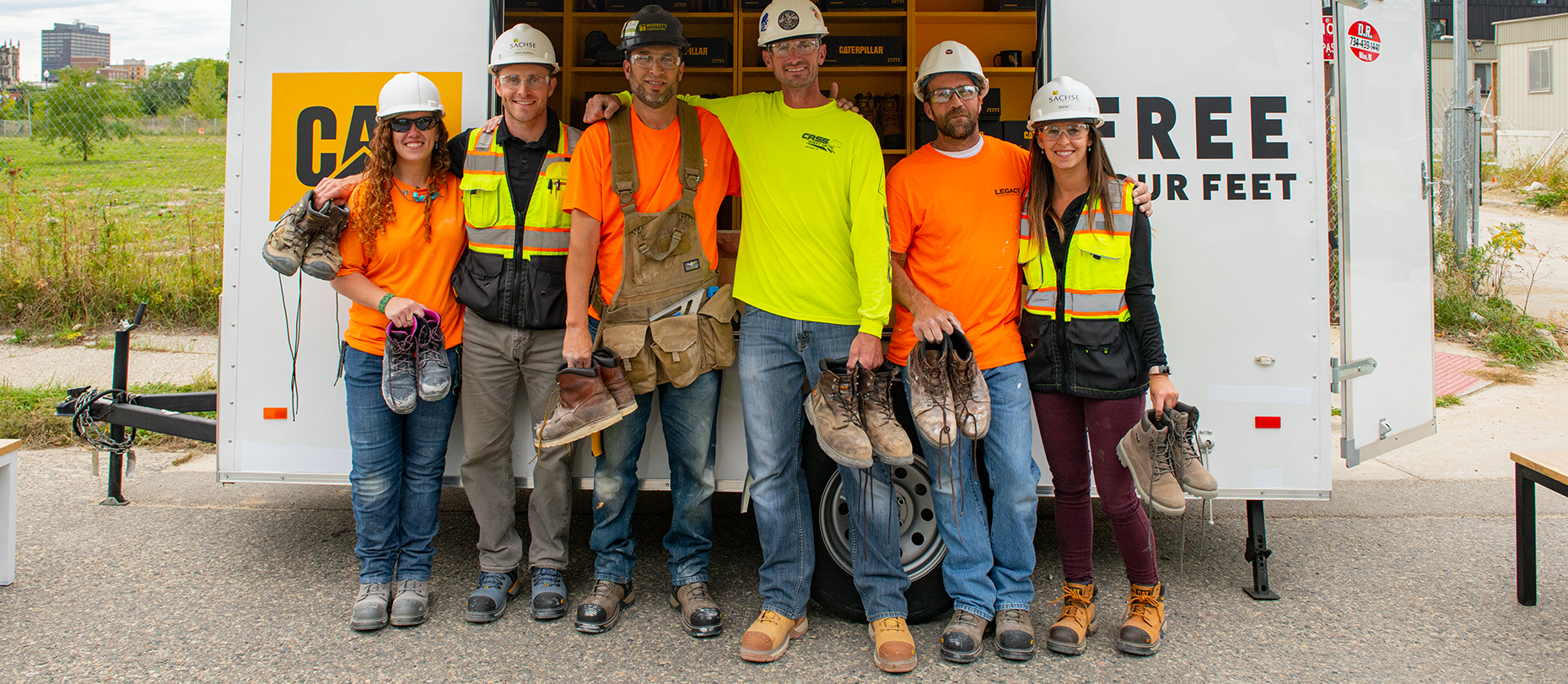 A group of workers in hard hats, who are very satisfied with thier CAT superlite boots.