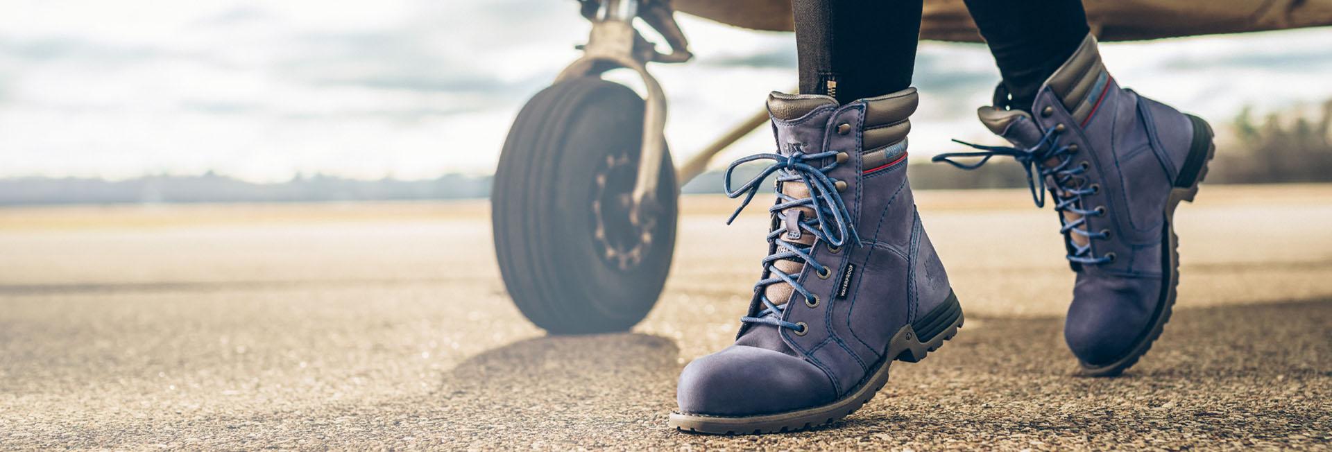 Boots walking on a runway beside a plane.