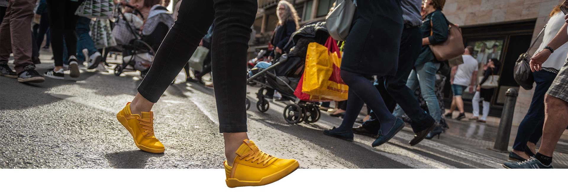 Yellow Code sneakers walking down a busy city street.
